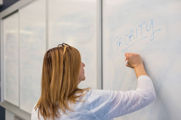 Woman writing on a white board trying to capture the priorities of her team.