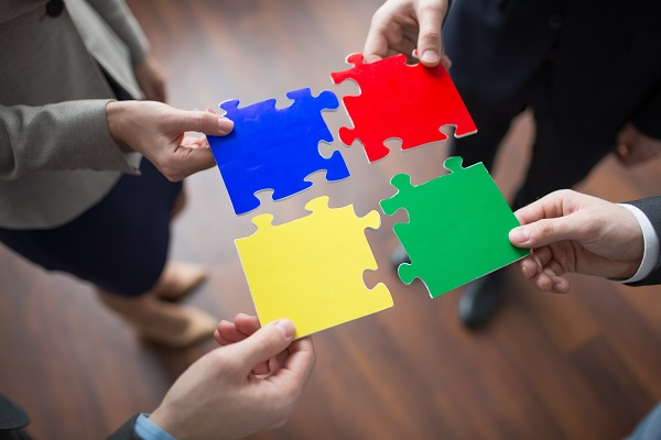 4 employees collaborating to put 4 different colour puzzle pieces together.